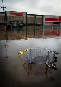 Police crime scene tape blew from an overturned shopping cart in the parking lot of an Oshman's sporting goods store in Irving after the shooting.