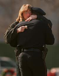 An unidentified woman hugged an Irving police officer at the graveside service.