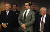 "George Rivas (center) listened to the charges read against him with his lawyers William E. ""Karo"" Johnson (left) and Wayne Huff beside on June 25, 2001."