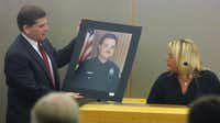 In court, Lori Hawkins (right) identified a picture of her slain husband held by  Dallas County prosecutor Toby Shook.