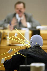 Dallas County Medical Examiner Jeffrey Barnard  testified during Donald Newbury's Dallas murder trial in January 2002.  Each yellow rod in the mannequin represented the angle of a bullet fired at  Hawkins.