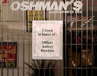 A sign on the front door of the Oshman's store in Irving where officer Aubrey Hawkins was slain on December 24, 2000.