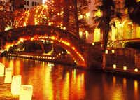 The light of luminarias adds a soft glow to the River Walk's glittery mix of festive decorations.