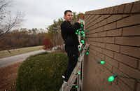 Cameron Livesay made sure his green lights were twinkling as he hung them at his home.