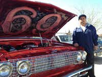 "Joe Ruiz posed proudly next to his cherry red 1987 Chevy truck, which is dressed up with parts from a 1960 Impala. The hood is popped open to reveal the truck's name, painted on the inside: ""69."""