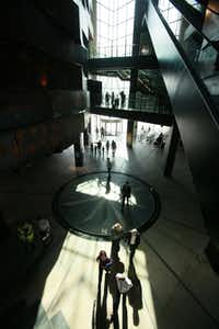 People walk in the main reception area in the Titanic Belfast visitor centre in Belfast, Northern Ireland.  A century after the Titanic sank on its maiden voyage, Belfast is counting on a new visitor attraction about the iconic ship to put the city that built it back on the tourist map.