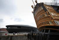 The Mary Rose Museum is located next to HMS Victory (R) in the Solent off Portsmouth, England. The Mary Rose was a warship of the Tudor navy of King Henry VIII. She sank in the Solent  on July 19, 1545 during an invasion by the French fleet. The wreck of the Mary Rose was rediscovered in 1971 and salvaged in 1982. The Mary Rose Museum in Portsmouth's Historic Dockyard is the new home to warship, and some of the 19,000 artifacts that sank with her.