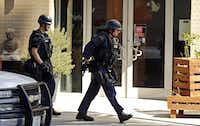 Police officers walked around a corner during the standoff. Much of Victory Park and the surrounding area was put on lockdown, including two schools, the AT&T Performing Arts Center, the Perot Museum and the Dallas World Aquarium.G.J. McCarthy  -  Staff Photographer