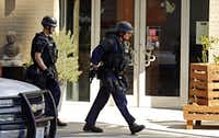Police officers walked around a corner during the standoff. Much of Victory Park and the surrounding area was put on lockdown, including two schools, the AT&T Performing Arts Center, the Perot Museum and the Dallas World Aquarium.( G.J. McCarthy  -  Staff Photographer )
