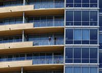 A man watched the police activity below from a balcony.G.J. McCarthy  -  Staff Photographer