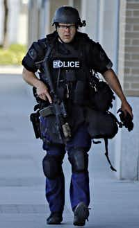 A police officer walked along Victory Plaza Lane during the standoff.G.J. McCarthy  -  Staff Photographer