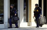 Police officers carried cases as they entered a building during a standoff with an armed man.( G.J. McCarthy  -  Staff Photographer )