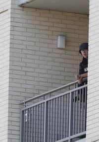 Dallas SWAT team members observed the scene from a balcony.( Michael Ainsworth  -  Staff Photographer )