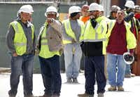 Construction workers watched where a gunman held police at bay.Michael Ainsworth  -  Staff Photographer