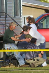 Relatives of victims in a shooting rampage comfort each other outside a home on March 10, 2009, in Samson, Ala. Michael McLendon fatally shot his mother and nine others before killing himself.