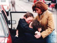 An unidentified mother and father embrace their uninjured daughter outside the elementary school in Dunblane, Scotland, on March 13, 1996. Thomas Hamilton killed 16 children and their teacher before turning the gun on himself.