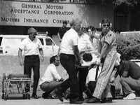Rescue workers attend to one victim as another is moved to a waiting ambulance on June 18, 1990, after James Edward Pough killed eight people and wounded six more before killing himself at a GMAC office in Jacksonville, Fla.