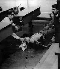 An unidentified person attends to a wounded woman on Dec. 6, 1989, at Montreal's Ecole Polytechnique College. Marc Lepine fatally shot 14 women before turning the gun on himself.