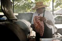 Pit master Clyde Biggins hoists a rack of pork ribs onto his largest smoker in front of his Dallas home to smoke overnight. Seasoned with only a blend of salt, pepper and chili powder, he denounces many of the more complex rubs and marinades commonly used today.