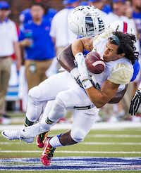 Baylor wide receiver Lynx Hawthorne holds on to a reception as he has his helmet knocked off by a hit from SMU linebacker Kyran Mitchell during the first quarter of an NCAA football game at Ford Stadium on Sept. 4, 2015, in Dallas. (Smiley N. Pool/Staff Photographer)