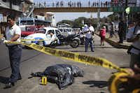 Police officers secure the area where human remains inside a plastic bag were dumped on a street in Acapulco, Mexico, on Saturday, Jan. 29. Once a glamorous beach mecca for international tourism, Acapulco's image has steadily deteriorated as a fierce turf war continues between rival drug gangs.