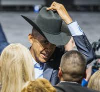 President Barack Obama tries on a cowboy hat from a member of the crowd after speaking at a Democratic National Committee event at Gilley's Club Dallas on Saturday, March 12, 2016 in Dallas. (Ashley Landis/Pool photo, The Dallas Morning News)