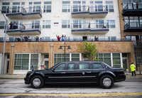 People cheer from apartment balconies as President Barack Obama passes in a presidential limousine on S Lamar St after speaking at a Democratic National Committee event at Gilley's Club Dallas on Saturday, March 12, 2016 in Dallas. (Ashley Landis/Pool photo, The Dallas Morning News)