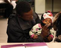 Anthony Smith held his 10-month-old daughter, Antoinette, while waiting for legal aid at the school. St. Philip's services also include a day care, a pediatric clinic, senior citizens' programs and after-school kids' programs in sports, dance, theater and music.(Rose Baca - Staff Photographer)