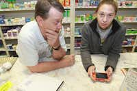 Pharmacist Mike Sulak and his daughter, Jill Vrla, show a graphic of the blast zone and Sulak's devastated home. Sulak worked Thursday to fill replacement prescriptions for customers at West Drug Store on Main Street.