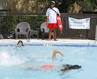 Lifeguard Memo Washington keeps an eye on a group of swimmers at the Lakefront Villas Apartment in Richardson.( Staff photo by RON BASELICE   -  DMN )