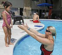 Nara Lindgren, 3, receives encouragement from Emily Wright to jump into the pool.( Staff photo by RON BASELICE   -  DMN )