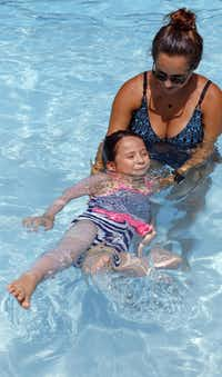 Instructor Abby Demers helps Azul Correa, 5, float.( Staff photo by RON BASELICE   -  DMN )