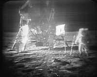 TV monitors showed Apollo 11 astronaut Neil Armstrong (right) trudging across the surface of the moon as Buzz Aldrin stood nearby. Roberts made it possible for the public to hear Armstrong's famous words in real time.