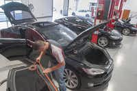 Rick Hynes, a Tesla vehicle technician,  replaces the weather stripping on the sunroof lid on a Tesla S model at the electric car company's  service center in Farmers Branch.
