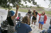 Volunteer Elisabeth Jordan, with her hand on Julio Martinez, led a prayer at the conclusion of a recent Bible study with some of Dallas' homeless. The Thursday sessions, led by CitySquare resident pastor Jonathan Grace and volunteers, are held on corners and lots between the Austin Street Center and City Square's new social service center.( Kye R. Lee  -  Staff Photographer )