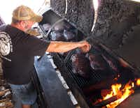 Pitmaster Robert Reid tends to the ribs on the smoker at Miller's Smokehouse in Belton. Ribs are available only Fridays and Saturdays.