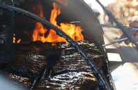 Pitmaster Robert Reid tends to the ribs on the smoker at Miller's Smokehouse.