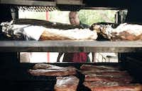 Owner and pit master Ben Washington checks his main pit at Whup's Boomerang Barbecue in Marlin.