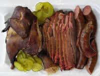 """Our lunch including chicken, brisket and sausage at Whup's Boomerang Barbecue. """"There are no high notes,"""" Posse member Bryan Gooding said of the bland rub on the brisket, ribs and chicken."""