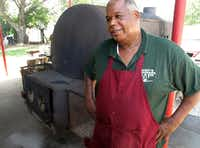 Owner and pit master Ben Washington chats with Posse members as he stands beside his main pit at Whup's Boomerang Barbecue.