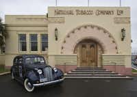 A Packard Six car sits outside Napier, New Zealand's 1933-built National Tobacco Company Building, designed by architect Louis Hay to fuse deco and art nouveau features.
