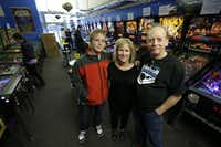 In this Dec. 16, 2013 photo, Charles Martin, right, poses for a photo with his wife Cindy, center, and their son Michael, left, on the main level of the Seattle Pinball Museum in Seattle. The Martins own and operate the museum, which allows visitors who pay the admission fee to play unlimited rounds on the machines, which range from the 1960s to modern-day games.