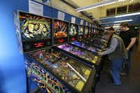 In this Dec. 16, 2013 photo, visitors play pinball on more modern machines at the Seattle Pinball Museum in Seattle.