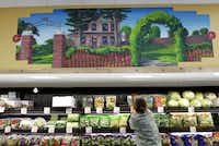 A mural of the Plano Heritage Farmstead Museum on display in front of Tiphany Barnett stacking produce at Trader Joe's in Plano on September 6, 2012.