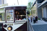 Riders wait to board Petunia, one of the McKinney Avenue Transit Authority trolleys, along St. Paul Street near Klyde Warren Park.