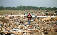 Mark Wade of Vilonia, Ark., looked through debris Tuesday after deadly tornadoes ripped through the region. At least 15 people in the state were killed as a tornado ripped through the region Sunday.(Mark Wilson - Getty Images)