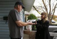 Volunteer Carmen Brito delivered a meal to John Lavender in Garland. (Rose Baca/The Dallas Morning News)