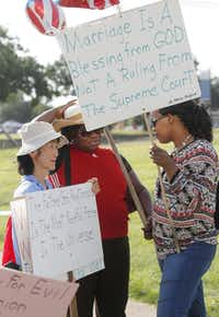 Members of the Universal Peace Federation, including (from left) Yuri Hernandez, Lucie Muleki and Odette Bilolo, talked as they prepared to march in the Independence Day Parade in Irving.( Michael Ainsworth  -  Staff Photographer )