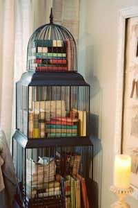 PIles and piles of vintage books make their home in a triple-decker bird cage.