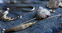 Bronze shawl pin (right), bronze leaf orifice hook for a spinning wheel (left) and other fired precious metal clay pieces made by Metal Clay Artist Jenny Vestal.